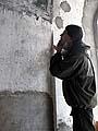 Георгий Кожокарь рассматривает найденное граффити в храме на Секирной горе. Фото 2006 г.