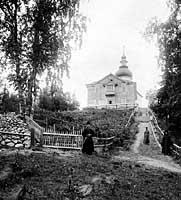 Двухэтажный келейный корпус (1890 г.) и церковь в честь Вознесения Господня с монастырским маяком (1862 г.) на горе Секирная
